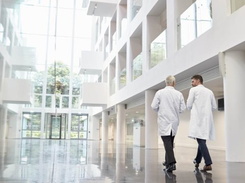 Two doctors walk in a modern hospital