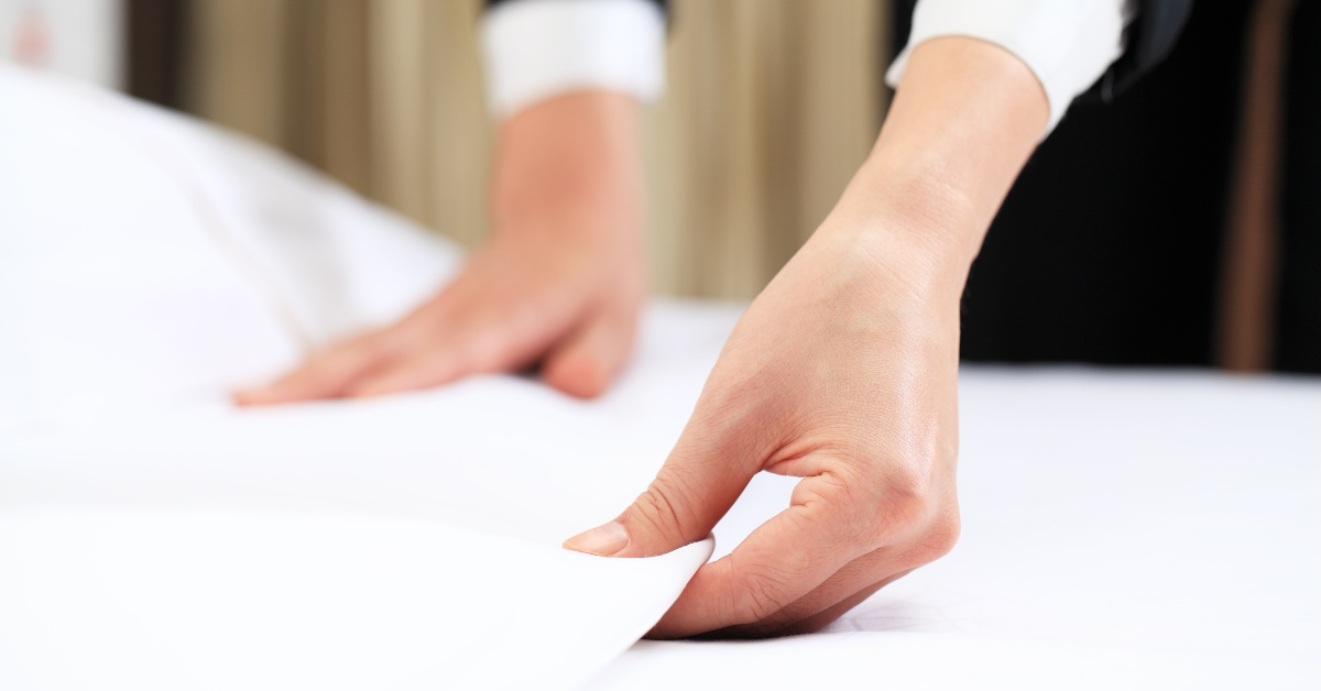 Hotel housekeeper folding the sheets of a crisp white bed