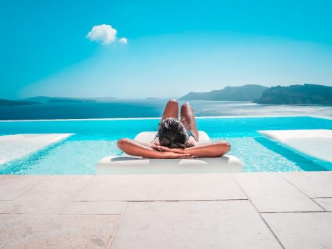 Woman relaxing by the pool of a luxury hotel