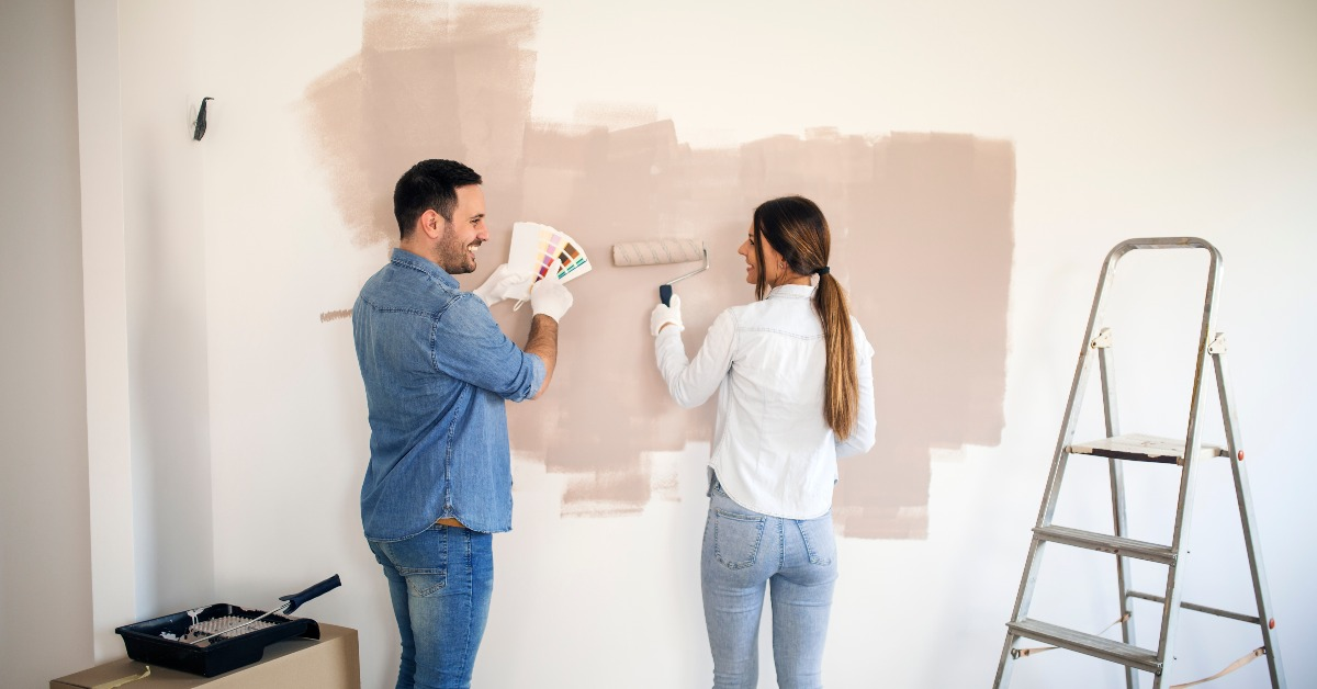 Couple painting their apartment wall